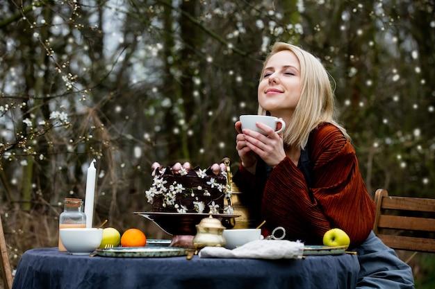 정원에서 차를 마시는 아름다운 여자