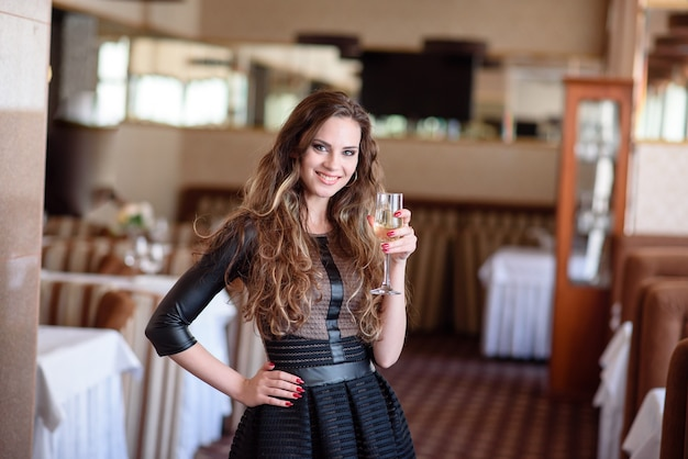 Красивая женщина пьет шампанское в ресторане