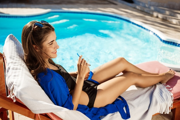 Beautiful woman drinking cocktail, lying on chaise near swimming pool