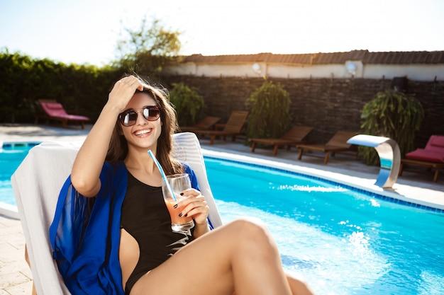 カクテルを飲み、スイミングプールのそばの長椅子に横たわっている美しい女性