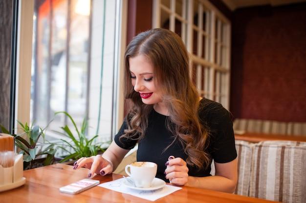 Красивая женщина пьет кофе и смотрит в телефон