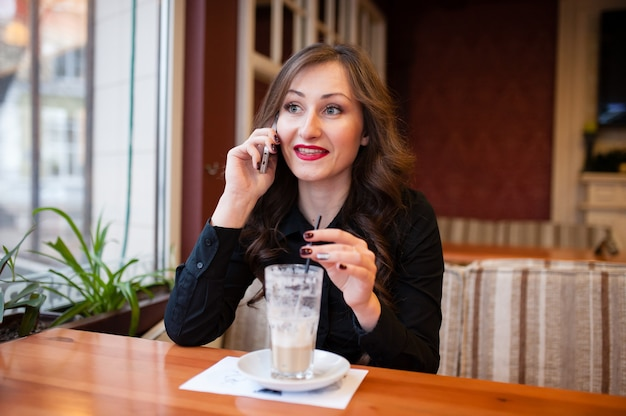 Красивая женщина пьет кофе и разговаривает по телефону