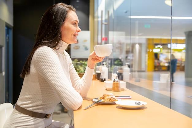 カフェのバーでコーヒーを飲む美しい女性