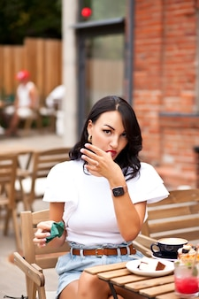 Beautiful woman drinking coffee in a cafe and eating croissant