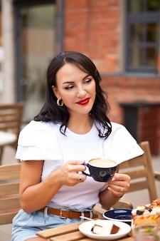 カフェでコーヒーを飲み、クロワッサンを食べる美女