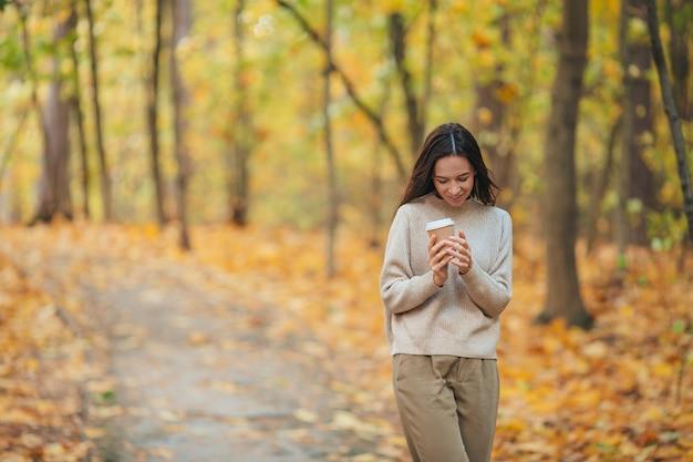 Красивая женщина пьет кофе в осеннем парке под осенней листвой