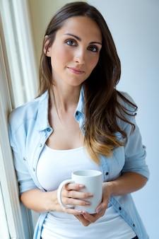 窓の近くの朝のコーヒーを飲む美しい女性。