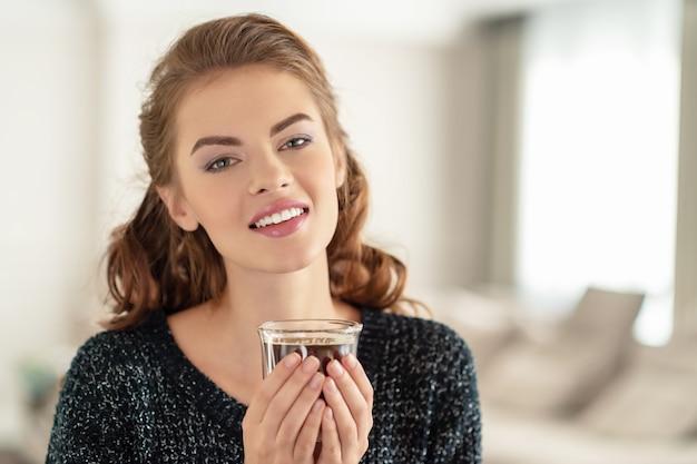 Bella donna che beve il caffè la mattina a casa