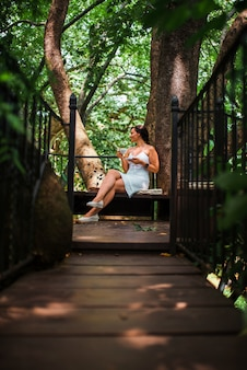 Beautiful woman drinking coffee in a treehouse cafe.