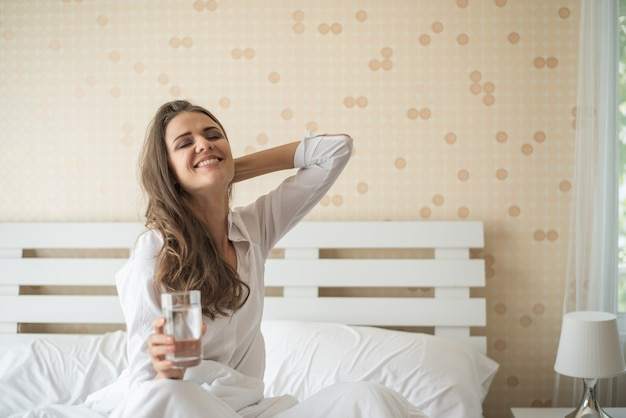 Beautiful woman drinking fresh water in the bed at the morning