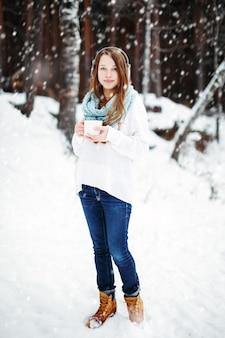 降雪の下でウィンターパークで温かい飲み物を飲む美しい女性。冬の休日のコンセプト。フルハイト、カメラを見て。