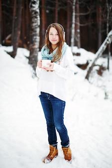 ウィンターパークで温かい飲み物を飲む美しい女性。冬の休日のコンセプト。フルハイト、カメラを見て。背景の冬の風景。