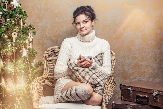 크리스마스 인테리어에 베개가 있는 의자에 앉아 차나 커피를 마시는 아름다운 여성 프리미엄 사진