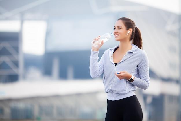 Красивая женщина пьет воду и слушает музыку после бега
