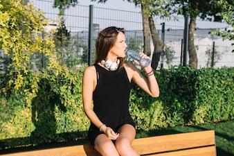 Beautiful woman drinking water in park