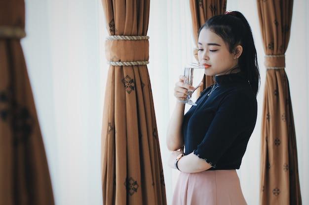 Beautiful woman drinking water near window