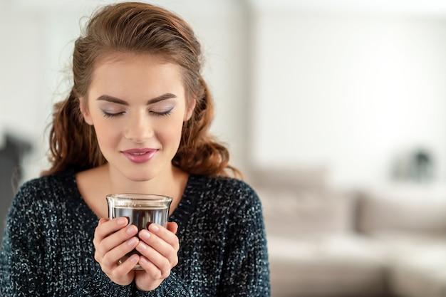아름 다운 여자는 커피를 마시고 맛을 즐기고 있습니다. 차 한잔과 함께 편안한 꽤 젊은 성인 소녀.