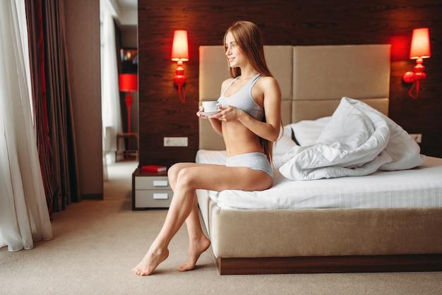 Beautiful woman drinks coffee in bed, good morning