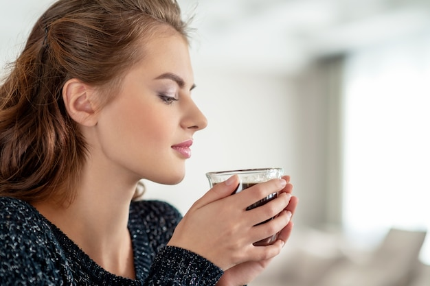 Beautiful woman drinks coffee and enjoying the taste. pretty young adult girl relaxing with cup of tea.