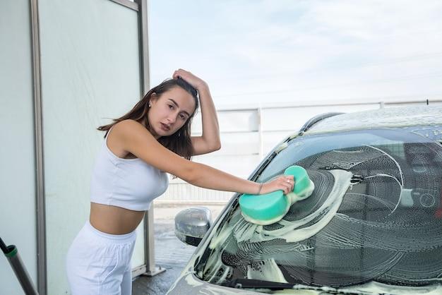 手動カーサービスウォッシュの美しい女性ドライバーは、スポンジの白い泡を使用して彼女の自動車の汚れをきれいにします