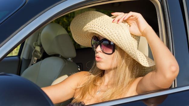 Красивая женщина-водитель в соломенной шляпе сидит на жарком солнце с опущенным окном автомобиля