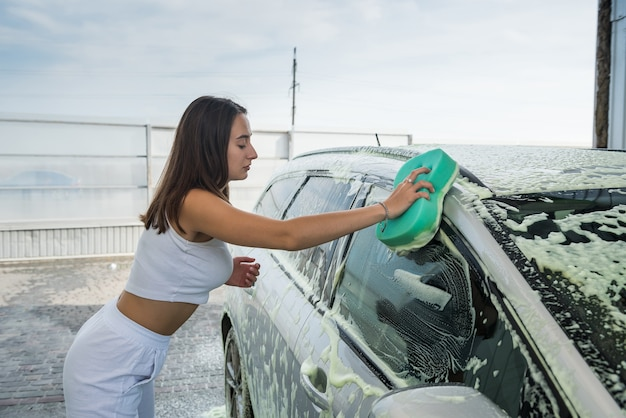 Beautiful woman driver washing windshield with sponge in clean foam on her dirty car at manual station