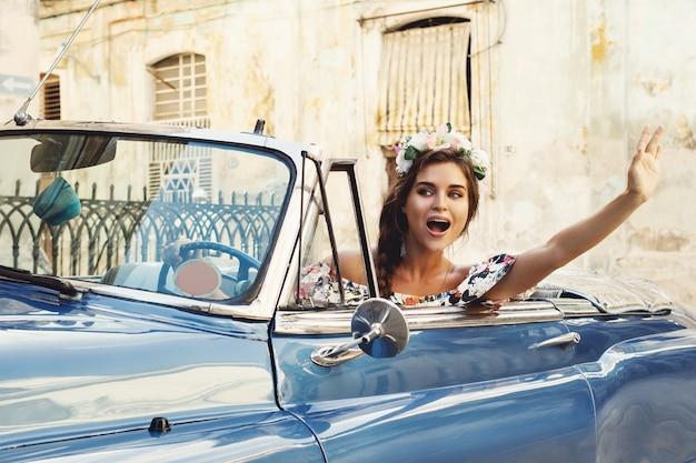 하바나 시내에서 복고풍 컨버터블 자동차를 운전하는 아름 다운 여자