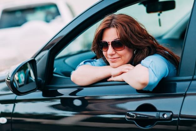 彼女の車を運転する美しい女性