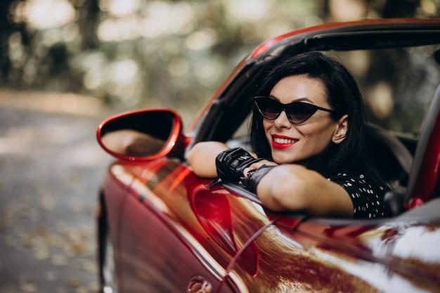 Красивая женщина за рулем красного кабриолета