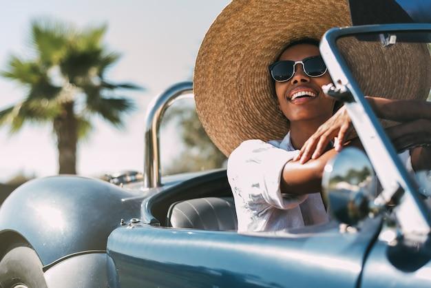 Beautiful woman driving a vintage convertible car