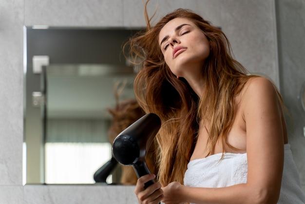 Beautiful woman drying her hair in the bathroom