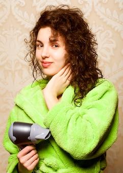 Красивая женщина сушит волосы феном