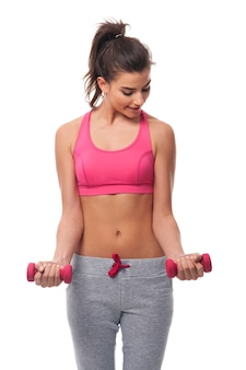 Beautiful woman during the workout with dumbbells