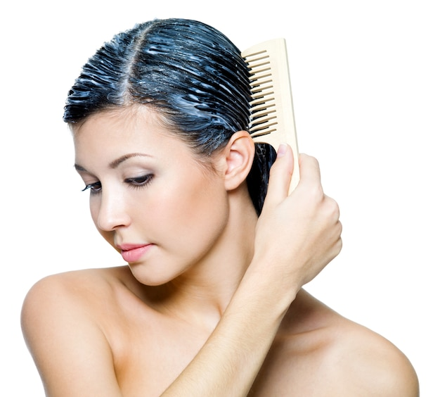 Beautiful woman dyeing hairs and combing them - on white