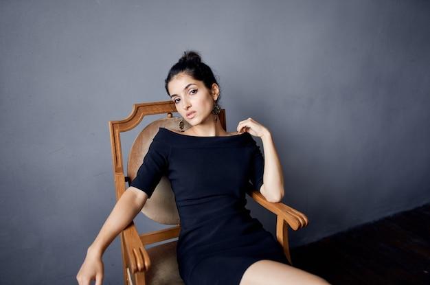 椅子の近くでポーズをとって美しい女性のイヤリングジュエリー黒いドレス孤立した背景