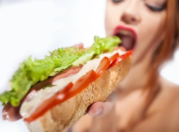 Красивая женщина ест хот-дог