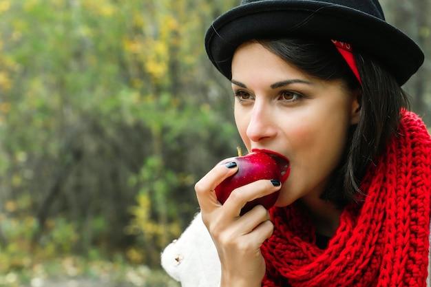 잘 익은 빨간 사과를 먹는 아름 다운 여자. 크로 셰 뜨개질 빨간 스카프와 검은 모자, 야외 피크닉