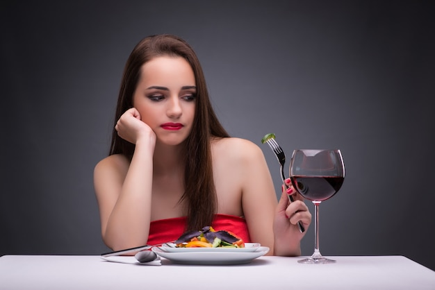 Beautiful woman eating alone with wine
