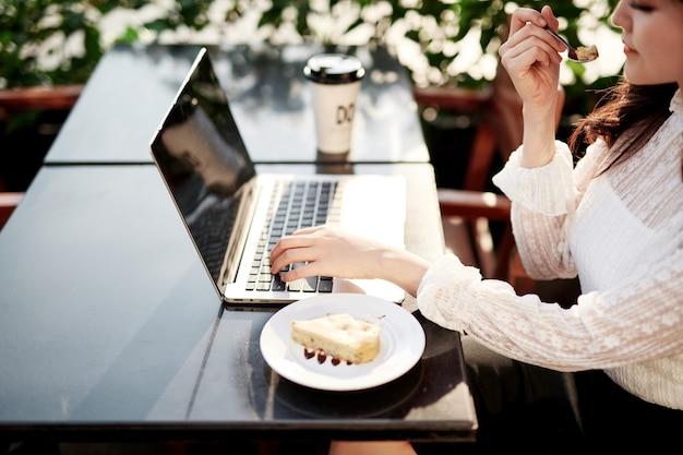 コーヒー ショップでおいしいバナナ ケーキを食べる美しい女性