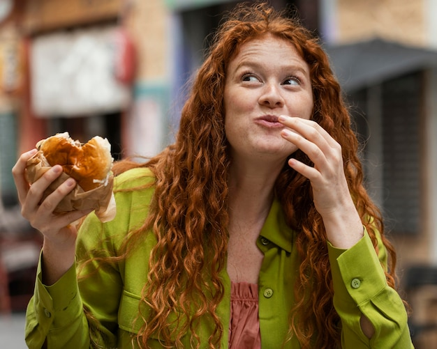 Beautiful woman eating delicious street food outdoors