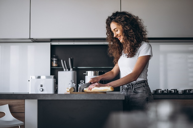 Beautiful woman eating fresh bread at the kitchen