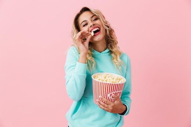 Красивая женщина ест попкорн из ведра, изолированного над розовой стеной