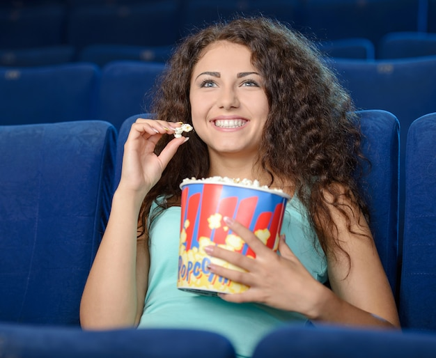 Beautiful woman eating popcorn while watching movie.