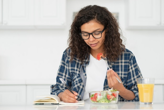 Beautiful woman eating salad and writing