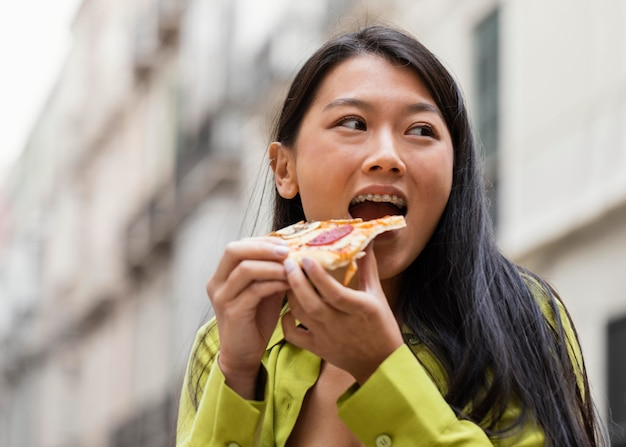 Beautiful woman eating street food outdoors