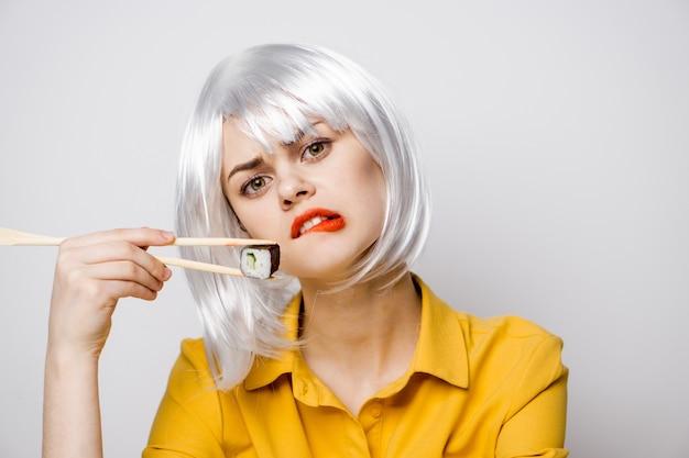 テーブルで出前から寿司やロールを食べる美女