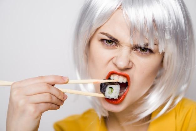 テーブルで巻き寿司を食べて美しい女性