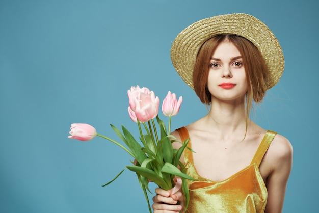美しい女性のエレガントなスタイルの楽しいライフスタイルの花束の花青い背景。
