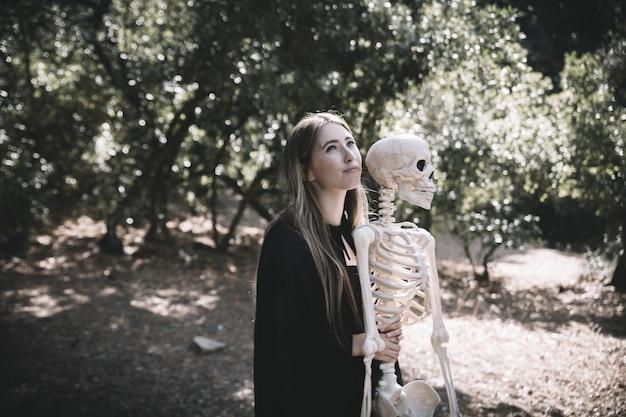 Beautiful woman embracing behind skeleton