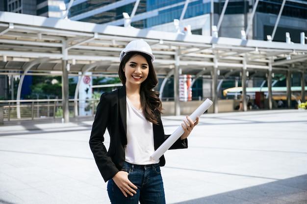 Красивая женщина инженер, холдинг бумажный план стоит перед промышленным зданием фон